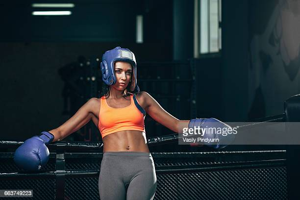 Female boxer leaning on ropes in boxing ring