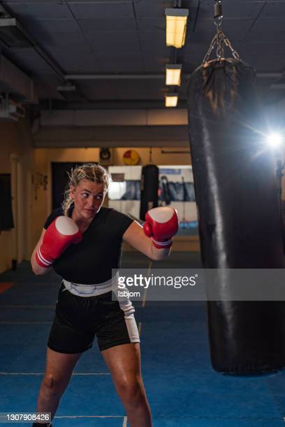 female boxer on a sports training in a gym - mixed martial arts stock pictures, royalty-free photos & images