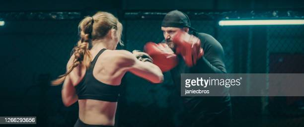 female boxer pad work session with trainer. quick punch and dodge - mixed martial arts stock pictures, royalty-free photos & images