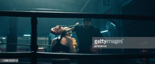 female boxer pad work session with trainer. quick punches in boxing ring - martial arts stock pictures, royalty-free photos & images