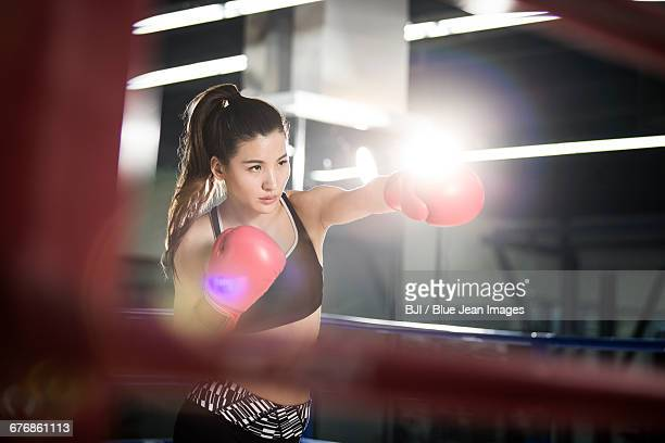 Female boxer practicing in boxing ring