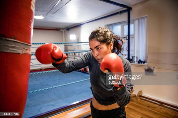 female boxer punching a punch bag - women's boxing stock pictures, royalty-free photos & images