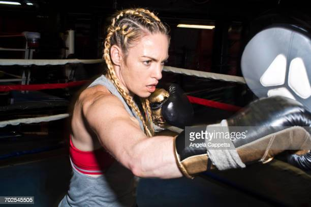Female boxer punching boxing mitt in boxing ring