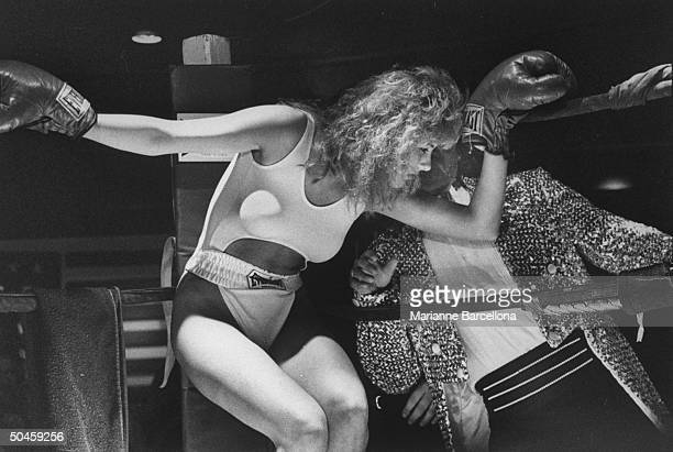 Female boxer Sasha Allen taking advice in the ring from obscured emcee Billy Dean, of Billy Dean's Foxy Boxer Revue at American Clubhouse.