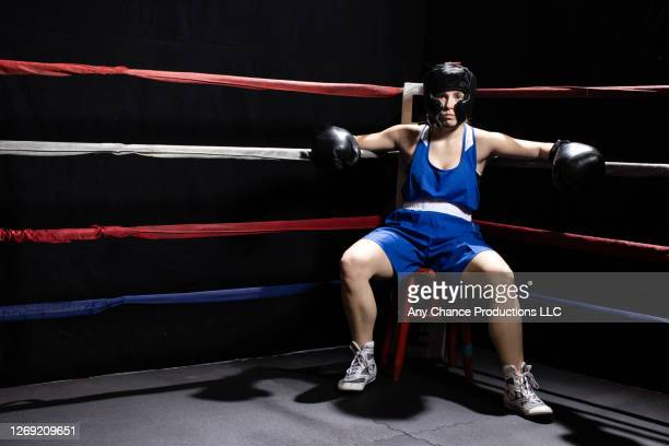 female boxer sitting on stool in her corner at the end of a round during sparring. - taking a corner stock pictures, royalty-free photos & images