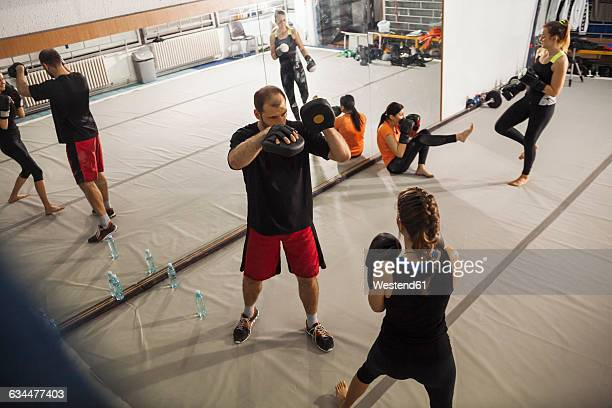Female boxer sparring with coach