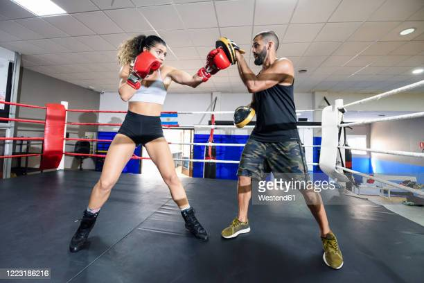 female boxer sparring with her coach in gym - women's boxing stock pictures, royalty-free photos & images