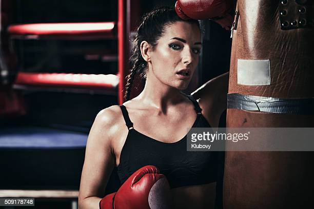 Female boxer standing by a punching bag