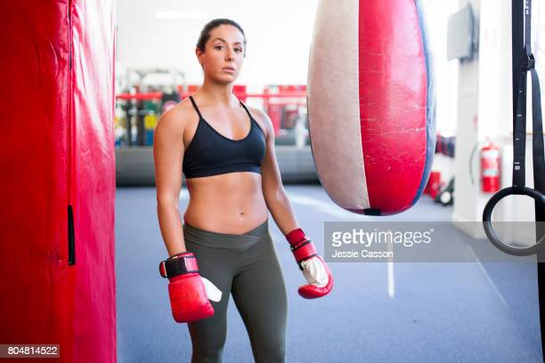 Female boxer stands next to punch bag in gym with boxing gloves on