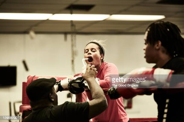 female boxer taking drink of water during practice - boxing stock pictures, royalty-free photos & images