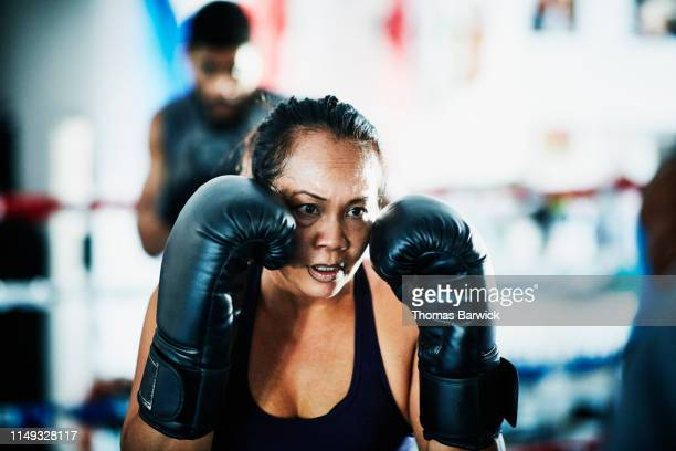Female boxer training in boxing ring in gym