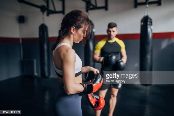 vrouwelijke bokser opleiding met haar mannelijke coach in de sportschool - slaan met vuist stockfoto's en -beelden