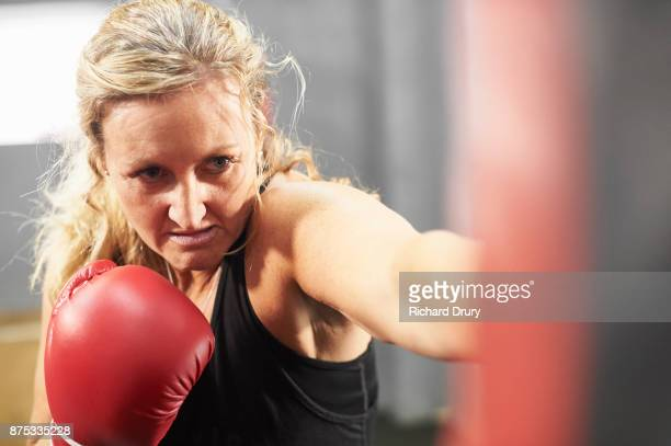 Female boxer training with punchbag