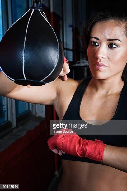 Female boxer using punch bag