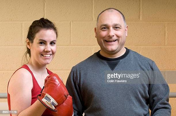 female boxer with instructor gym