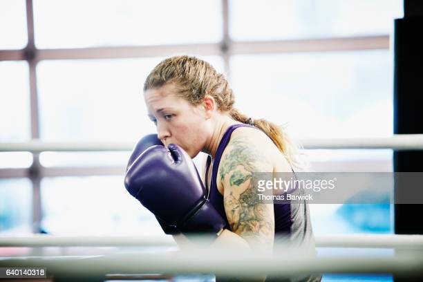 Female boxer working out in ring in gym