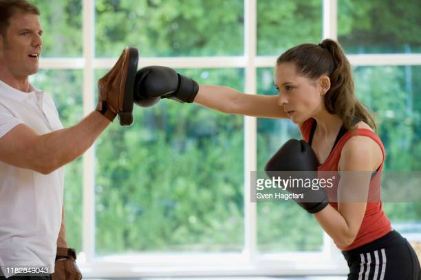 a female boxer working with a trainer - boxing shorts stock pictures, royalty-free photos & images
