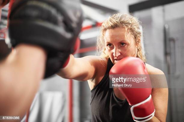 female boxer working with personal trainer - ボクシング 女性 ストックフォトと画像