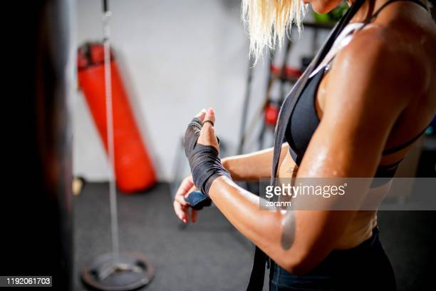 female boxer wrapping bandage around her hands - strap stock pictures, royalty-free photos & images