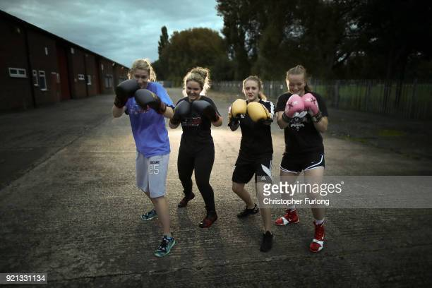 Female boxers Charliegh Carter aged 22 Ellie Hyde Nicola Sayer and Olivia Hussey all aged 16 pose with their boxing gloves during training at the...