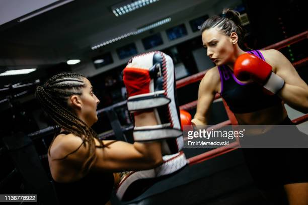 female boxers having a fight in the ring during sports training - mixed martial arts stock pictures, royalty-free photos & images