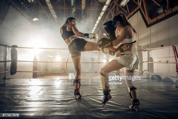 Female boxers having a fight in the ring during sports training.
