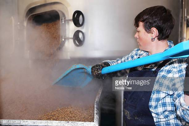 female brewer emptying grain from tank