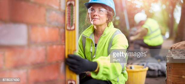 female brickie checking her levels