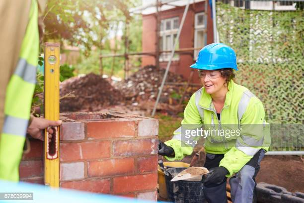 female bricklayer with colleague