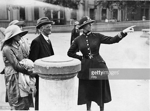 A female British Metropolitan Police officer points as she gives directions to a family of visitors from out of town London 1920s
