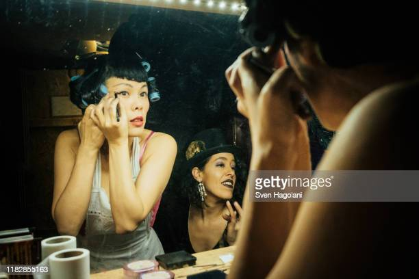 female burlesque performers getting ready, applying makeup at dressing room mirror - backstage stock pictures, royalty-free photos & images