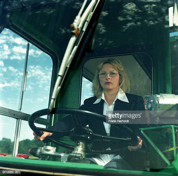Female bus driver at wheel, view through windscreen, portrait