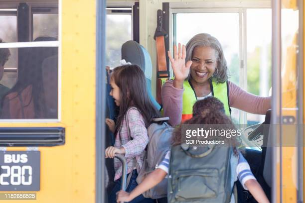 female bus driver high-fives children boarding bus - school bus stock pictures, royalty-free photos & images