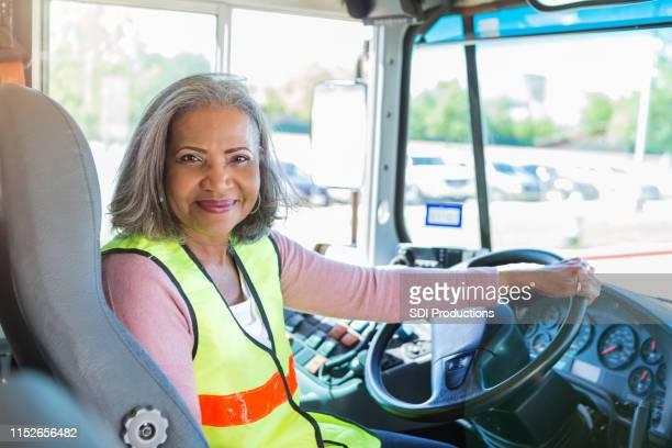 female bus driver looks at camera confidently - school bus stock pictures, royalty-free photos & images