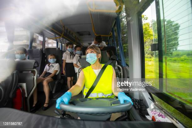 covid-19. female bus driver transporting elementary school kids by bus. - school bus stock pictures, royalty-free photos & images
