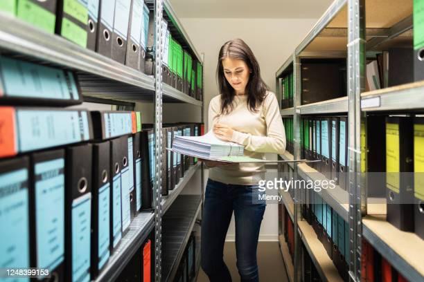 金融ファイルアーカイブのドキュメントを管理する女性ビジネス会計士 - 法的手続 ストックフォトと画像