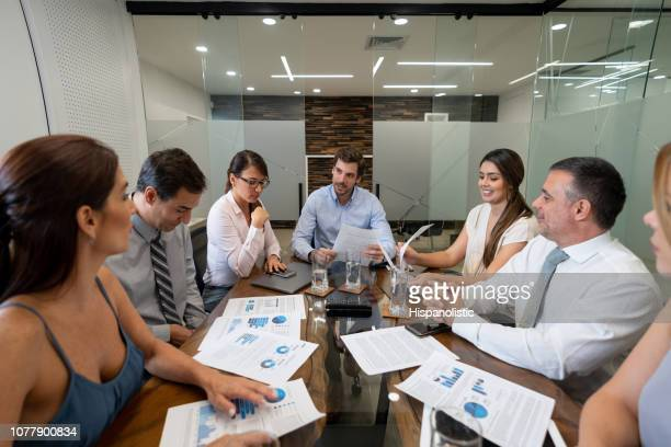 female business colleague addressing an issue talking to male leader while everyone listens happy - hispanolistic stock photos and pictures