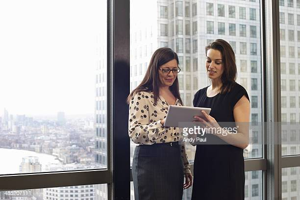 female business colleagues looking at digital tablet in office - hauptstadt stock-fotos und bilder