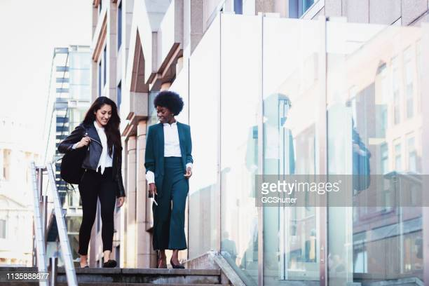 female business colleagues rushing to office - outdoors stock pictures, royalty-free photos & images