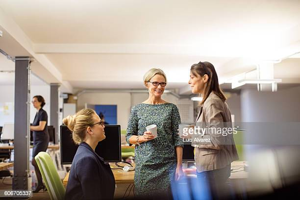 female business colleagues talking in coffee break - vier personen stock-fotos und bilder