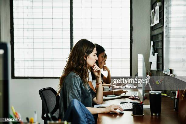 female business colleagues working at computers in design studio - デザインスタジオ ストックフォトと画像
