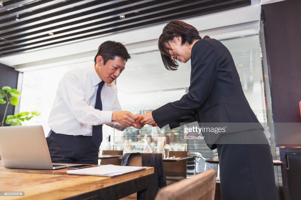 Female business executive handing over her card to the businessman : Stock Photo