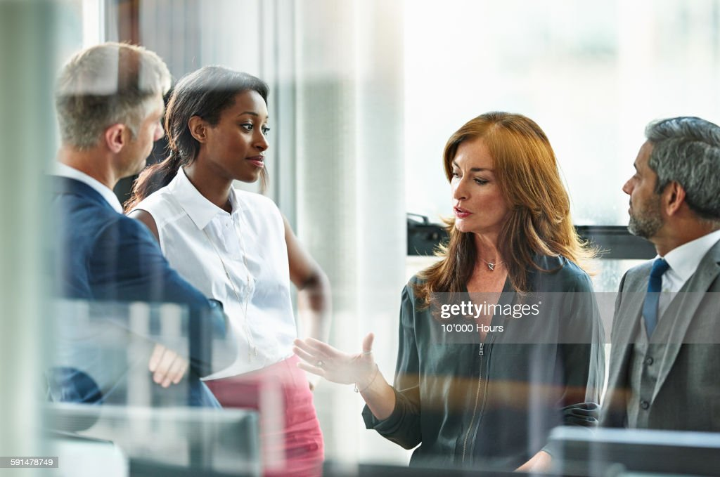 Female business executive leading team meeting : Stock Photo