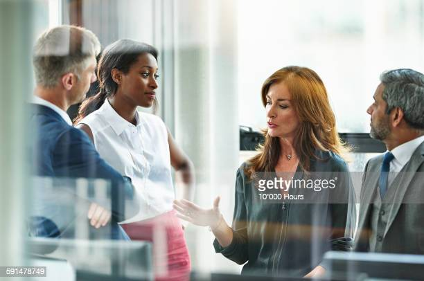 female business executive leading team meeting - leanincollection stock pictures, royalty-free photos & images