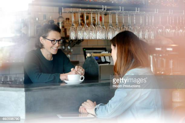 Female business owner chatting to customer