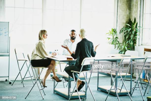 Female business owner leading project meeting with employees in design studio conference room