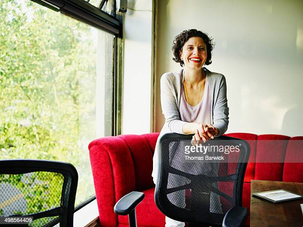 Female business owner leaning against chair