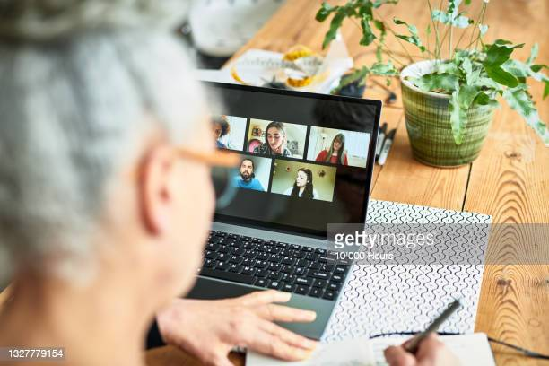 female business owner making notes in front of laptop showing virtual team meeting - working seniors stock pictures, royalty-free photos & images