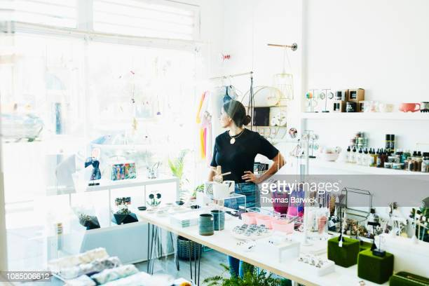 Female business owner standing in boutique looking out window