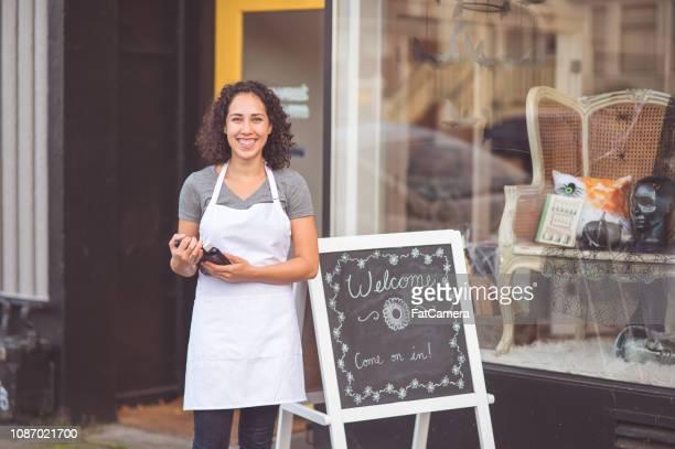 vrouwelijke ondernemer staat op de stoep buiten haar salon - openingsevenement stockfoto's en -beelden